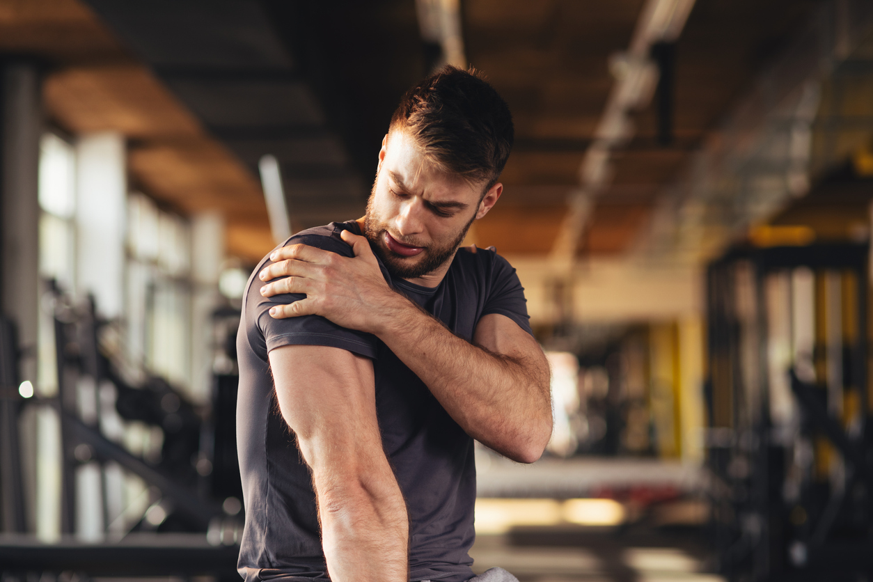Man at gym trying to exercise after an injury to his shoulder