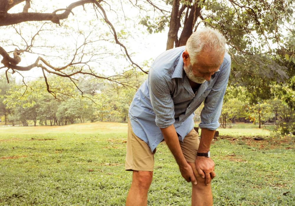 an older man in park bending over and gripping knee